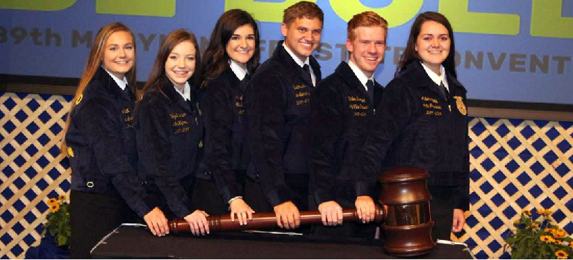6 students in matching blazers hold a giant gavel