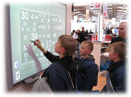 students and a teacher work on a math problem on an electronic smart board