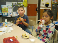 2 children eat breakfast in their classroom