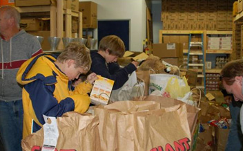 Students fill bags at a local food bank to be given to community residents in need.